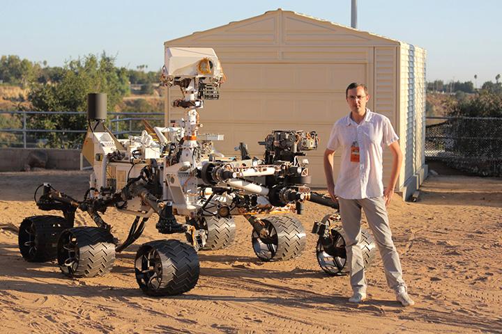 Астрофизик Алексей Вареников позирует рядом с марсоходом Curiosity
