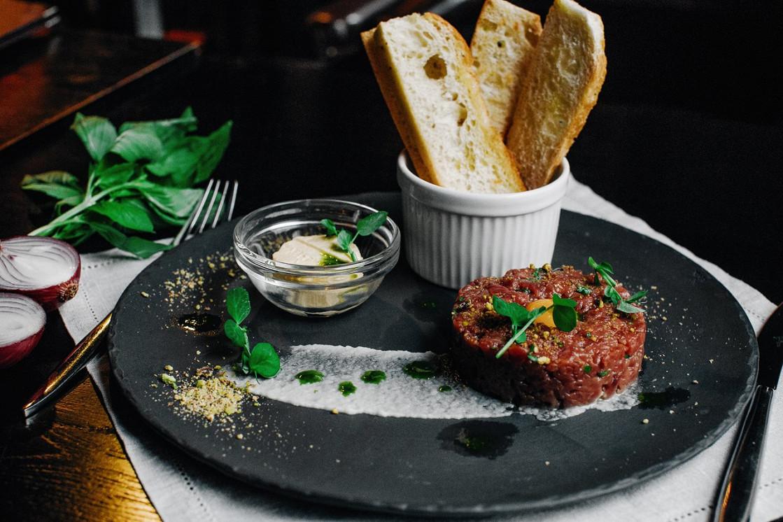 Ресторан Franky - фотография 1 - Представляем вашему вниманию тар-тар из нежнейшей говядины - блюдо основного меню. В нашем случае подается с пряными тостами из пшеничного хлеба и сливочным маслом с зеленью.