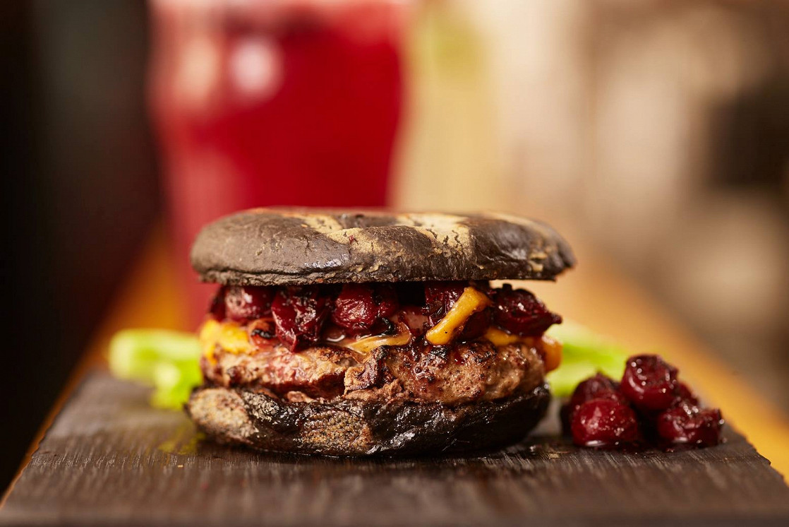 """Ресторан Burger Heroes - фотография 3 - Фирменный бургер """"Черная мамба"""" с копченым на грушевых стружках беконом, сыром Чеддер и вишней в прованских травах"""