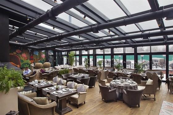 Ресторан Hills - фотография 10 - Зимний сад со стеклянной крышей и дровяным камином